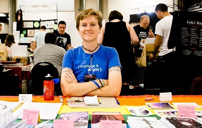 a photo of LB's vessel, a thin white person sitting at a comic con table, which is covered with a pride flag tablecloth and piles of home-printed comics